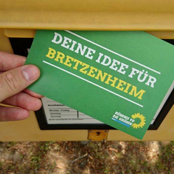 """Eine grüne Postkarte mit der Aufschrift """"Deine Idee für Bretzenheim"""" wird in einen Briefkasten eingeworfen."""